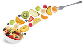 Eating flying fruit salad with fork, fruits like apples, oranges Stock Photos
