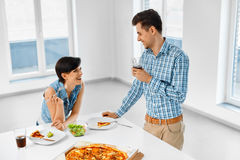 Eating Food. Happy Lovely Couple Eating Pizza Indoors. Leisure C Stock Photos