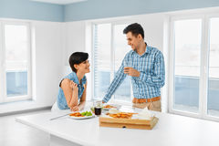 Eating Food. Happy Lovely Couple Eating Pizza Indoors. Leisure C Royalty Free Stock Photo