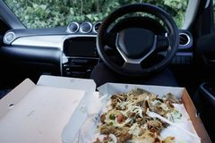 Eating food on the move in car due to busy stressful work life being unhealthy stock images