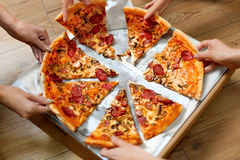 Eating Food. People Taking Pizza Slices. Friends Leisure, Fast F. Eating Food. Close-up Of People Hands Taking Slices Of Pepperoni Pizza. Group Of Friends Royalty Free Stock Photography