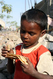 Eating Food in Poverty. A poor beggar boy from India looking at the stale bread he is eating stock images