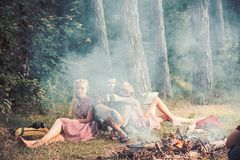 Eating food, reading book and entertainment. Friends relax at bonfire flame with smoke. People camping at fire in forest. Women and bearded men at campfire stock photo