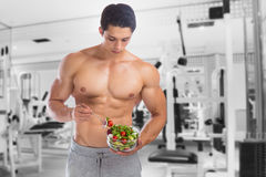 Eating food salad bodybuilding bodybuilder fitness gym body buil. Der building muscles young man studio Royalty Free Stock Photos