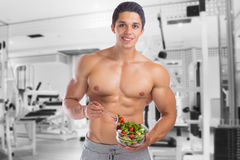 Eating food salad bodybuilding bodybuilder gym body builder buil. Ding muscles muscular young man studio Royalty Free Stock Photo