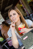 Eating french fries in fast food coffee shop or restaurant beautiful blond young woman with green eyes having fun, portrait Royalty Free Stock Photo