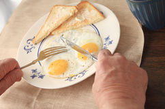 Eating fried eggs with buttered toast Stock Photos