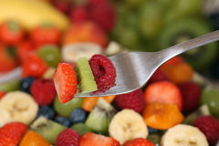 Eating fruit salad with fruits like strawberry, kiwi and raspber Stock Photography