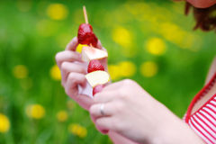 Eating a fruit skewer Royalty Free Stock Photography