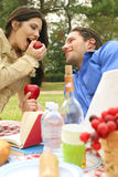 Eating Fruits On Summer Picnic. Two young people sharing fruits on picnic day stock images