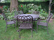 Eating in the garden. Chairs and a table in a garden setting Stock Images