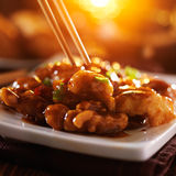 Eating general tso's chicken with chopsticks Royalty Free Stock Image