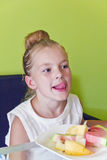 Eating girl with put out tongue Royalty Free Stock Photos