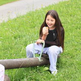 Eating girl on swing Royalty Free Stock Images