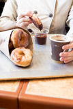 Eating glazed doughnuts with chocolate sauce Royalty Free Stock Photography