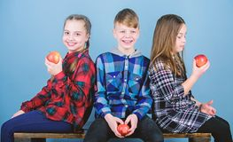 Eating good and feeling good. Happy small girls and boy holding red apples. Happy little kids eating and smiling. Together. Happy children. Enjoying happy stock photography