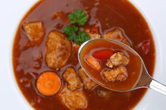 Eating goulash soup with meat and paprika on spoon from above Stock Image