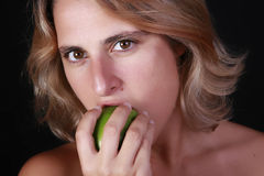 Eating a green apple. Portrait of a young beautiful woman eating a green apple Stock Photography