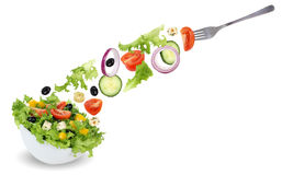 Eating green salad in bowl with fork, tomatoes, onion, olives an Stock Photo