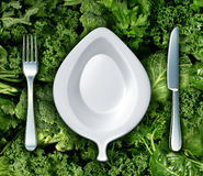 Eating Green Vegetables. And healthy diet concept with a fork knife and plate shaped as a leaf as a dinner setting on a group of dark leafy greens as a symbol Royalty Free Stock Image