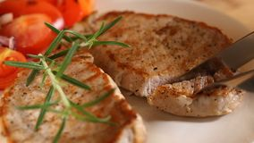 Eating grilled pork chop with vegetables stock footage