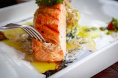 Eating grilled Salmon Steaks with Lime and baked spinach Royalty Free Stock Photos