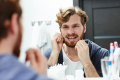 After eating habit. Young man flossing his teeth in front of mirror Royalty Free Stock Images