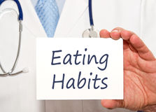 Eating Habits - Doctor with sign. Eating Habits - Doctor holding sign with text Royalty Free Stock Photography