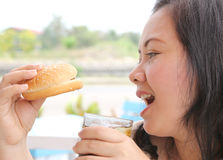Eating hamburger. Closeup image of asian woman eating hamburger at coffeeshop stock photography