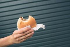 Eating hamburger. Delicious hamburger in the hands. Fastfood meal. Eating hamburger. Delicious hamburger in the hands. Fastfood meal Stock Photo