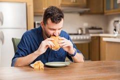 Eating a hamburger at home Stock Image