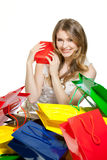 Eating an healthy apple. Young woman with a lot of shopping bags Stock Photos