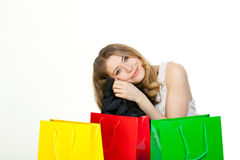 Eating an healthy apple. Young woman with a lot of shopping bags Stock Images