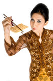 Eating healthy biscuit. A beautiful asian girl using chopsticks to eat a biscuit Stock Photography