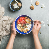 Eating healthy breakfast bowl over grey concrete background Royalty Free Stock Photography