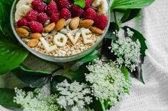 Eating healthy breakfast bowl. The word LOVE in a plate with a healthy meal. Raspberry, Banana, Nuts. Vegetarian food concept stock images