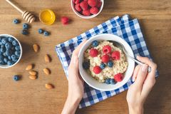 Eating healthy breakfast. Oatmeal porridge with berries in hands stock image