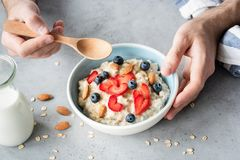 Eating healthy breakfast oatmeal porridge with fresh berries and nuts Royalty Free Stock Photos