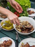 Women hand bbq, eating healthy fresh salad and barbecue meat at outdoor barbecue garden party gathering, selective focus. Eating healthy fresh salad and barbecue stock photos