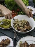 Women hand bbq, eating healthy fresh salad and barbecue meat at outdoor barbecue garden party gathering, selective focus. Eating healthy fresh salad and barbecue stock photography