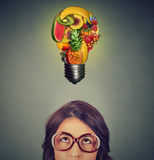 Eating healthy idea concept. woman looking up light bulb made of fruits above head. Eating healthy idea and diet tips concept. Closeup portrait headshot woman in Royalty Free Stock Image