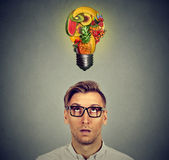 Eating healthy. Man looking up at fruit light bulb. Eating healthy and diet tips concept. Man looking up at fruit light bulb above head  on gray wall background Royalty Free Stock Photo