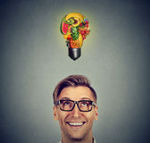 Eating healthy. Man looking up light bulb made of fruits Royalty Free Stock Photos