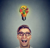 Eating healthy. Man looking up light bulb made of fruits. Eating healthy idea and diet tips concept. Portrait headshot man looking up light bulb made of fruits Royalty Free Stock Photo