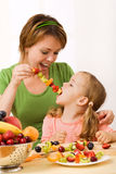 Eating a healthy snack - fruit slices on stick Royalty Free Stock Photo