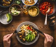 Eating healthy vegetarian meal in bowl with chick peas puree, roasted vegetables , red paprika tomatoes stew, avocado and seeds . Royalty Free Stock Image
