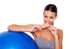 Eating her favorite after-workout snack. Cropped shot of attractive sporty woman sitting next to her fitness ball and eating a protein bar over white isolated Stock Photo
