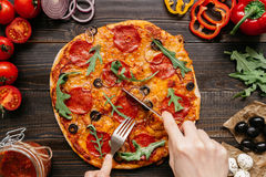 Eating hot delicious pizza, top view. Pizza ingredients on the wooden table stock photos