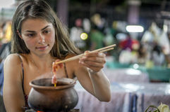 Eating from a hot pot. Girl eating local food having fun on travel in Asia Stock Photos