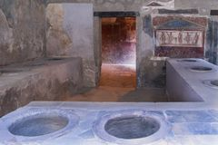 Eating house in Pompeii, Italy with serving counter and wall painting Royalty Free Stock Image